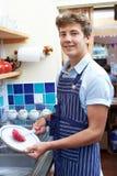 Adolescente con la tienda a tiempo parcial de Job Washing Up In Coffee Fotografía de archivo