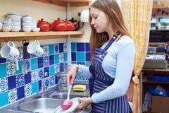 Adolescente con la tienda a tiempo parcial de Job Washing Up In Coffee Imagen de archivo