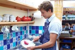 Adolescente con la tienda a tiempo parcial de Job Washing Up In Coffee Imagenes de archivo