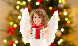 Adolescente con las alas del ángel y el regalo de la Navidad fotos de archivo libres de regalías