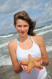Adolescente con las estrellas de mar en la playa Fotos de archivo libres de regalías