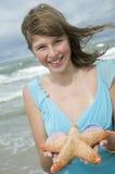 Adolescente con las estrellas de mar en la playa Imágenes de archivo libres de regalías