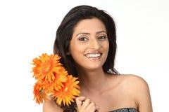 Adolescente con las flores de la margarita anaranjada Imagen de archivo libre de regalías