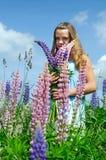 Adolescente con las flores del lupine Imagen de archivo