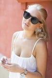 Adolescente con las gafas de sol usando el teléfono móvil Imagenes de archivo
