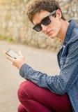 Adolescente con las gafas de sol usando un teléfono elegante Fotos de archivo libres de regalías