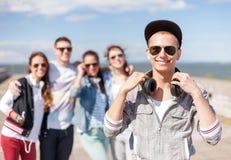 Adolescente con las gafas de sol y los amigos afuera Imagen de archivo