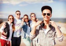 Adolescente con las gafas de sol y los amigos afuera Imagenes de archivo