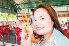 Adolescente con las gambas asadas a la parrilla, samui Tailandia Foto de archivo libre de regalías