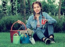 Adolescente con las herramientas que cultivan un huerto que se sientan en hierba en jardín Fotos de archivo