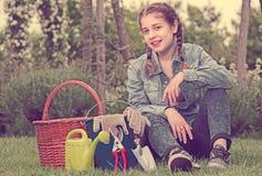 Adolescente con las herramientas que cultivan un huerto que se sientan en hierba en jardín Imagenes de archivo