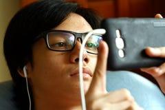 Adolescente con las lentes usando un smartphone Imagen de archivo