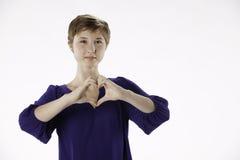 Adolescente con las manos en forma de corazón Foto de archivo libre de regalías