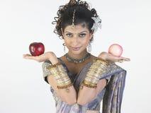 Adolescente con las manzanas de la explotación agrícola de la sari del diseñador Foto de archivo