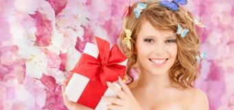 Adolescente con las mariposas en el pelo que muestra el presente Fotografía de archivo libre de regalías