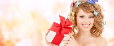 Adolescente con las mariposas en el pelo que muestra el presente Imágenes de archivo libres de regalías