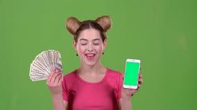 Adolescente con las notas de un teléfono y del papel en sus manos Pantalla verde almacen de metraje de vídeo