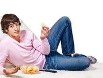 Adolescente con las patatas a la inglesa y teledirigido Fotografía de archivo