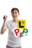 Adolescente con las placas del carnet de conducir que miran para arriba Fotografía de archivo libre de regalías