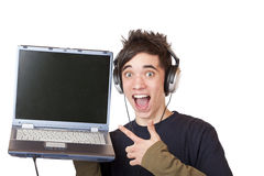 Adolescente con las puntas de los auriculares en la visualización de ordenador Imágenes de archivo libres de regalías