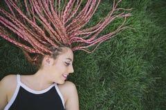 Adolescente con las trenzas rosadas en la hierba Fotos de archivo