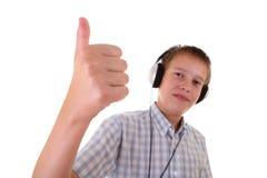 Adolescente con le cuffie che ride e che mostra BENE Fotografia Stock Libera da Diritti