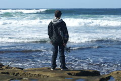 Adolescente con le onde di sorveglianza di skaterboard Fotografia Stock