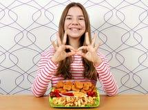 Adolescente con le pepite di pollo ed il segno della mano di approvazione fotografia stock libera da diritti