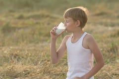 Adolescente con leche de consumo de los ojos cerrados Imagen de archivo libre de regalías