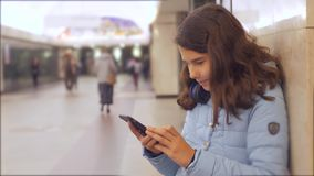 Adolescente con lo smartphone e le cuffie che aspettano il lotto del sottopassaggio dell'incrocio sotterraneo della folla della g stock footage