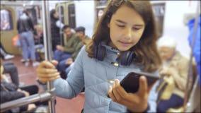 Adolescente con lo smartphone e le cuffie dentro un'automobile di sottopassaggio molto sottopassaggio sotterraneo della folla del archivi video