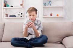 Adolescente con los apoyos en los auriculares que juegan a juegos en smartphone Imagen de archivo libre de regalías