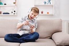 Adolescente con los apoyos en los auriculares que juegan a juegos en smartphone Foto de archivo libre de regalías