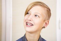 Adolescente con los apoyos en sus dientes Imagen de archivo