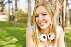 Adolescente con los auriculares en un parque Imágenes de archivo libres de regalías