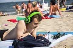 Adolescente con los auriculares que miran el teléfono Imagenes de archivo