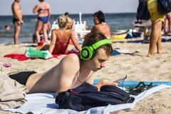 Adolescente con los auriculares que miran el teléfono Imagen de archivo libre de regalías