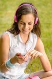 Adolescente con los auriculares que se sientan en hierba Fotografía de archivo libre de regalías