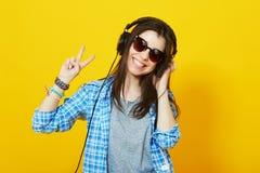 Adolescente con los auriculares que sonríe mostrando gesto de la paz Imágenes de archivo libres de regalías