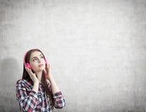 Adolescente con los auriculares rosados, concretos Imagen de archivo libre de regalías