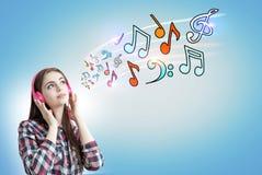 Adolescente con los auriculares rosados, notas, azules Fotos de archivo