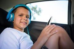 Adolescente con los auriculares usando la tableta digital en el asiento trasero del coche Imagenes de archivo