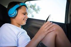 Adolescente con los auriculares usando la tableta digital en el asiento trasero del coche Foto de archivo