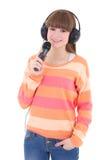 Adolescente con los auriculares y el micrófono aislados en blanco Fotografía de archivo libre de regalías