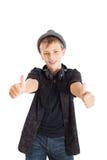 ¡Adolescente con los auriculares y el sombrero que muestran la muestra excelente! Foto de archivo libre de regalías