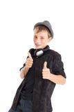¡Adolescente con los auriculares y el sombrero que muestran la muestra excelente! Imagenes de archivo