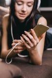 Adolescente con los auriculares y el teléfono elegante Foto de archivo
