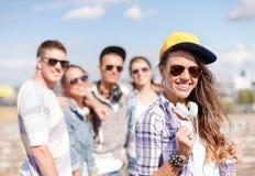 Adolescente con los auriculares y los amigos afuera Imágenes de archivo libres de regalías