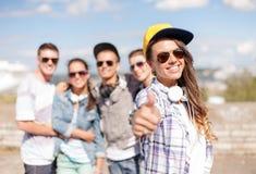 Adolescente con los auriculares y los amigos afuera Foto de archivo libre de regalías