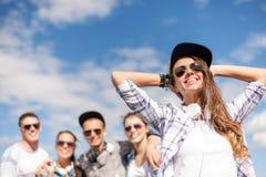 Adolescente con los auriculares y los amigos afuera Fotos de archivo